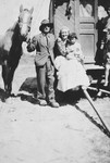 A Roma (Gypsy) family.  A woman and child are seated at the entrance to their caravan; a man stands next to them holding a horse.
