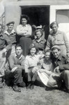 Group of men and women from the Jewish Brigade posing out side the door of a building.