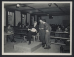 Defendant Dr. Klaus Schilling examines evidence on the stand in the Dachau trial.