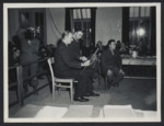 A witness examines evidence in the Dachau trial as prosecutor William Denson looks on.